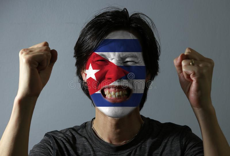 Cheerful portrait of a man with the flag of the Cuba painted on his face on grey background. stock image