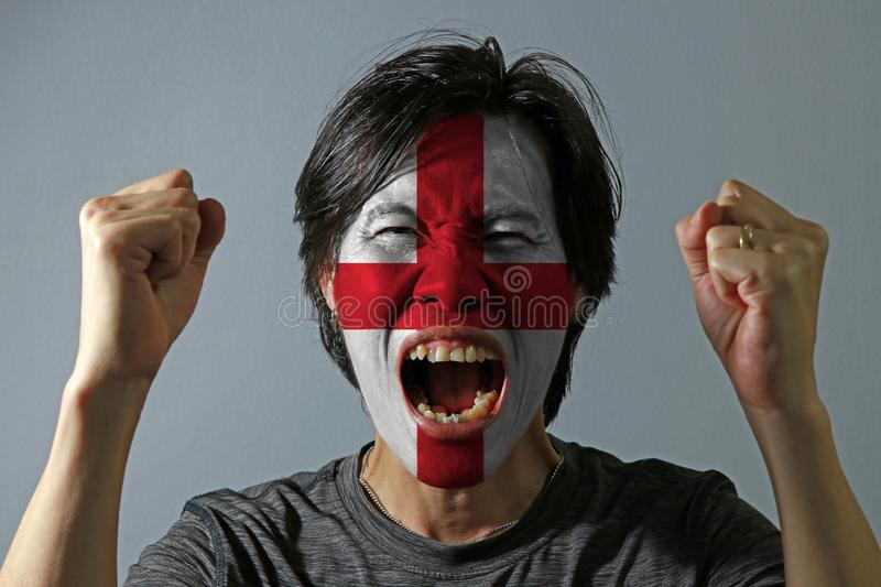 Cheerful portrait of a man with the flag of the England painted on his face on grey background. royalty free stock photography