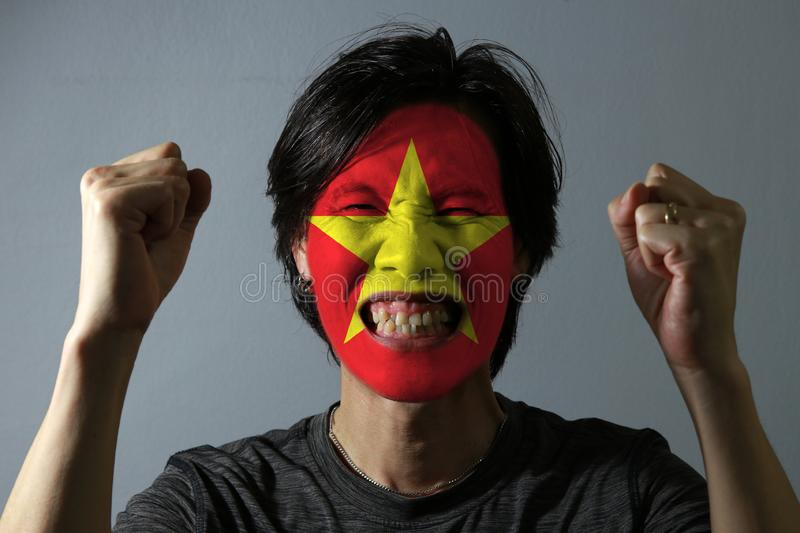 Cheerful portrait of a man with the flag of the Vietnam painted on his face on grey background. The concept of sport or nationalis royalty free stock photography