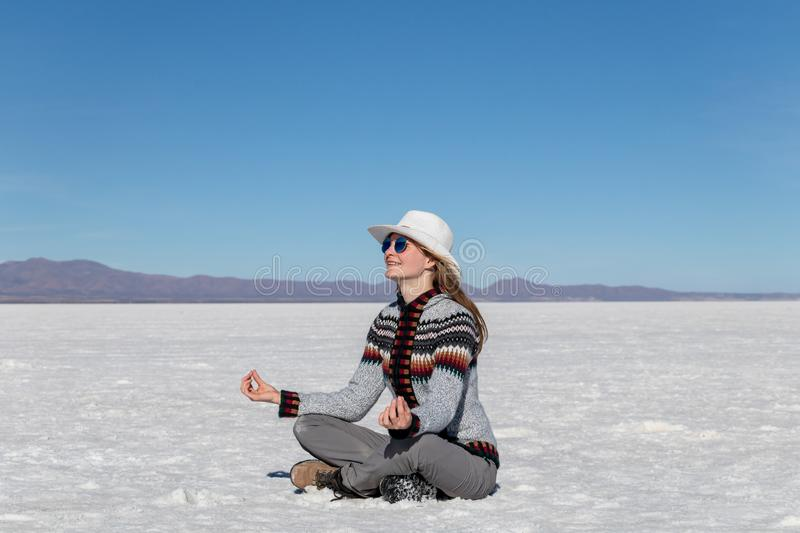 Cheerful positive blond girl clothing casual sitting at the salt flat desert Uyuni and meditating in yoga pose. Caucasian casual model wearing hat and stock image