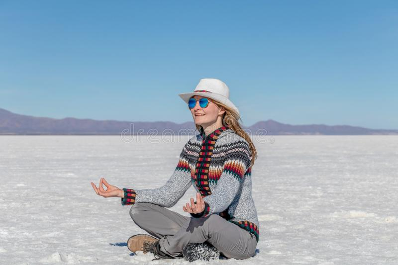 Cheerful positive blond girl clothing casual sitting at the salt flat desert Uyuni and meditating in yoga pose. Caucasian casual model wearing hat and stock photos