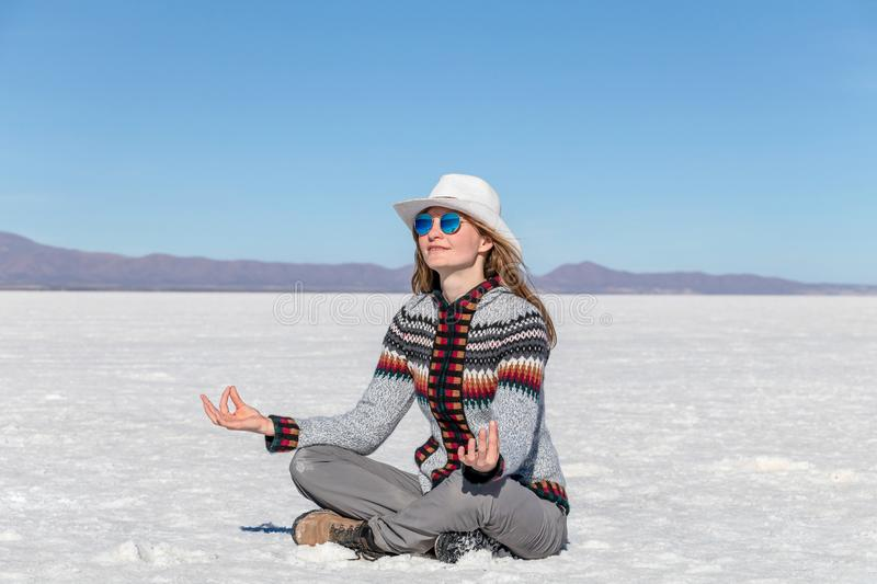 Cheerful positive blond girl clothing casual sitting at the salt flat desert Uyuni and meditating in yoga pose. Caucasian casual model wearing hat and royalty free stock images