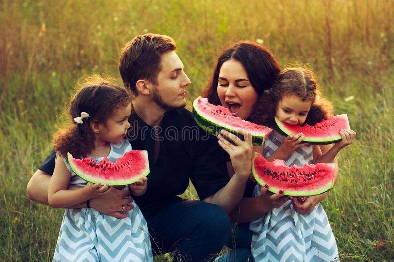 Cheerful positive family of four having a picnic and eating watermelon outdoors in a sunny weather. Curly beautiful twins sisters royalty free stock images