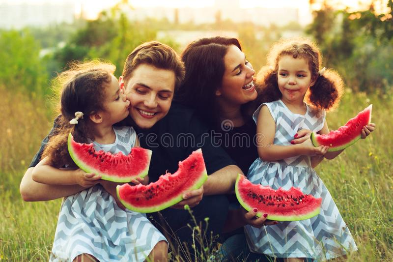 Cheerful positive family of four having a picnic and eating watermelon outdoors in a sunny weather. Curly beautiful twins sisters stock photography