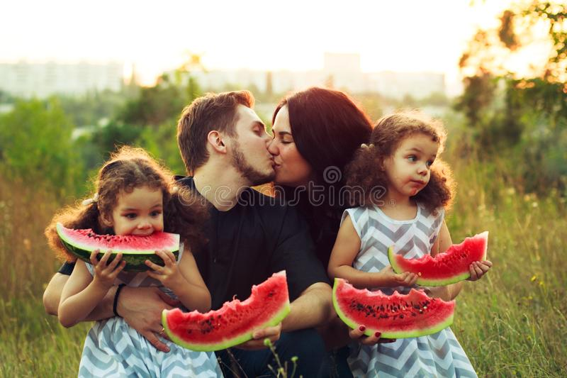 Cheerful positive family of four having a picnic and eating watermelon outdoors in a sunny weather. Curly beautiful twins sisters royalty free stock photo