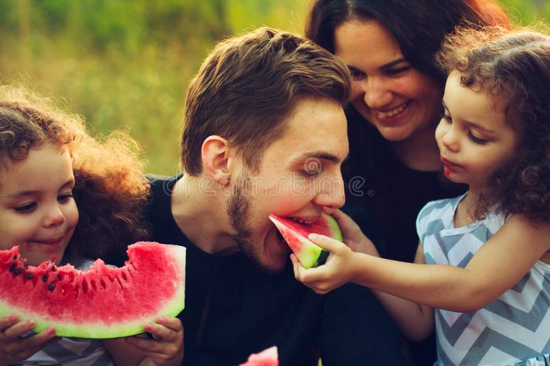 Cheerful positive family of four having a picnic and eating watermelon outdoors in a sunny weather. Curly beautiful twins sisters stock photo