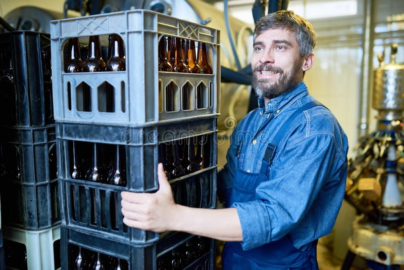 Happy brutal male mover working in beer warehouse stock photo