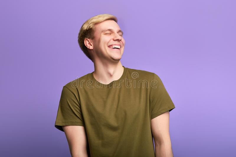 Cheerful positive man with closed eyes, laughs positively royalty free stock image