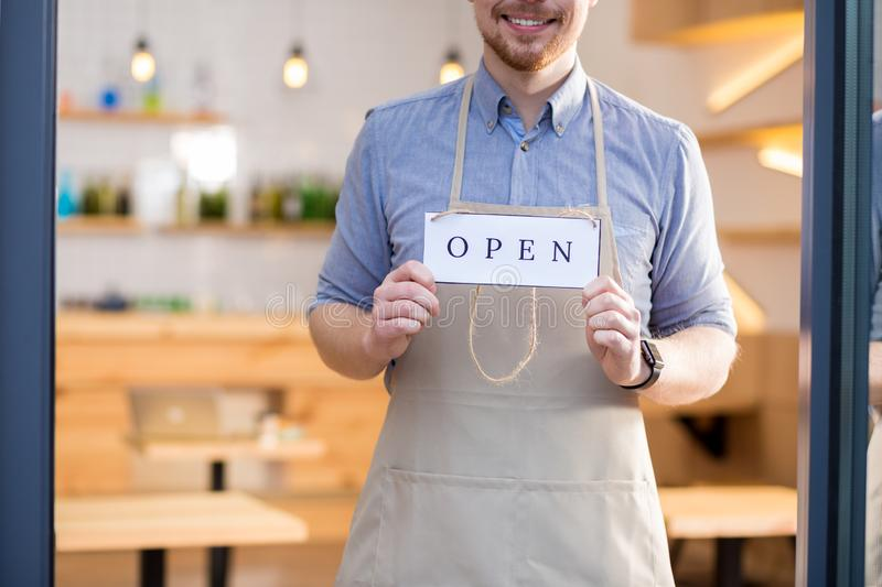 Cheerful positive man showing the label tag. Time to be open. Cheerful positive young men standing behind the glass door and holding the label tag while showing royalty free stock images