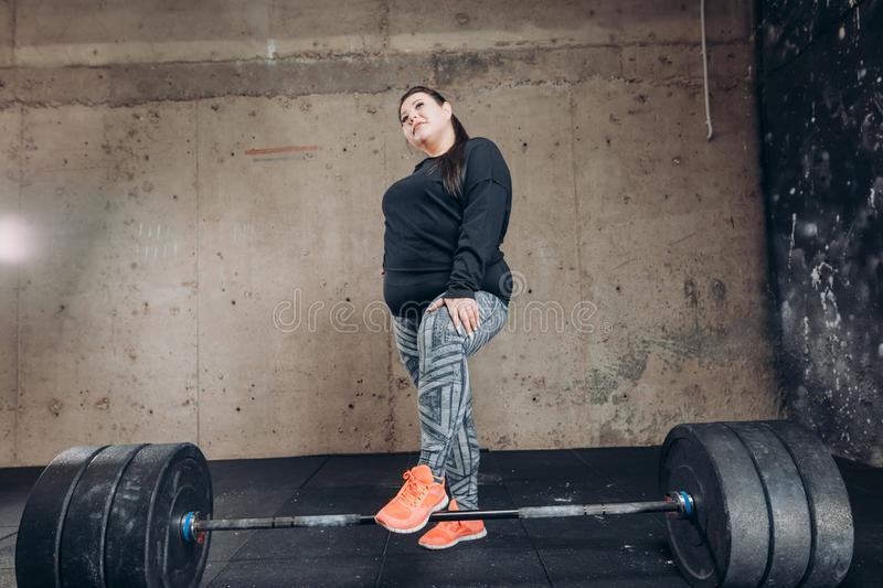 Cheerful positive obese girl standing next to the barbell. In the sport center. full length photo stock images