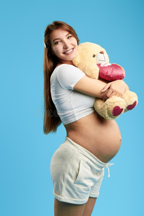 Cheerful positive pregnant woman with her teddy bare posing to the camera. Strong hug. isolated blue background. healthy pregnancy royalty free stock images