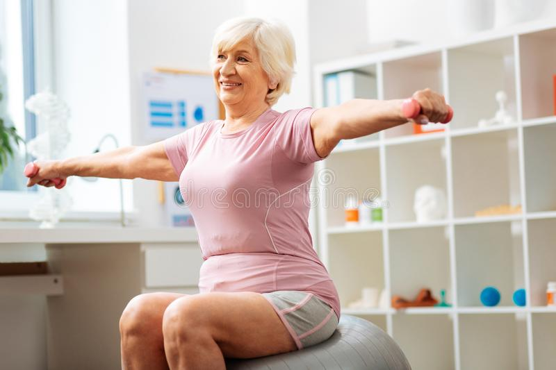 Cheerful positive woman doing exercises with dumbbells stock image