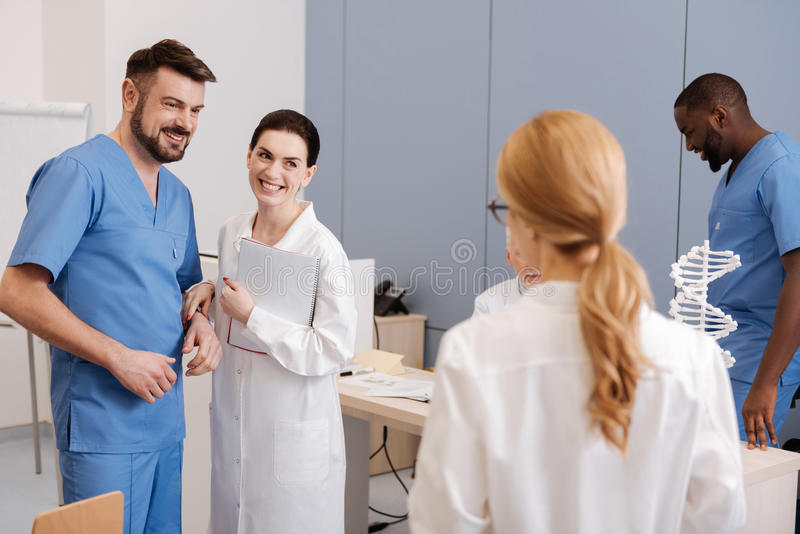 Cheerful practitioners taking part in medical conference at work. Pleasant process of exchanging experience. Smiling friendly experienced practitioners studying stock photo