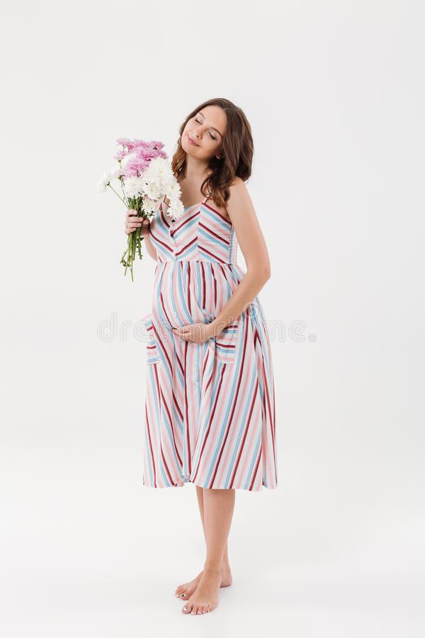 Cheerful pregnant woman holding flowers with eyes closed. royalty free stock photography