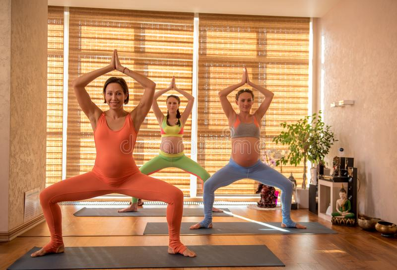 Cheerful pregnant women doing yoga stock image