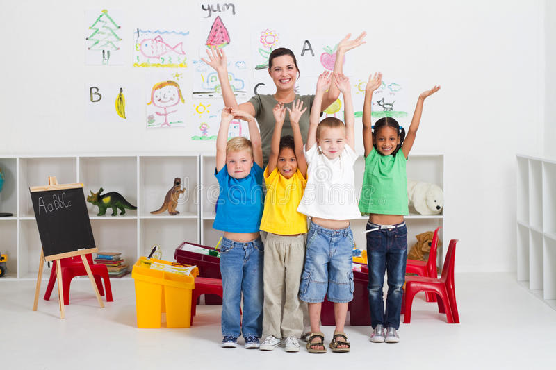 Cheerful preschool class. A happy cheerful prescshool class with their hands waving in the air in classroom stock images