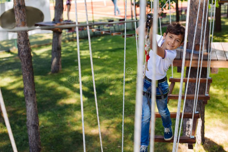 Cheerful preteen boy posing while climbing at rope park stock photo