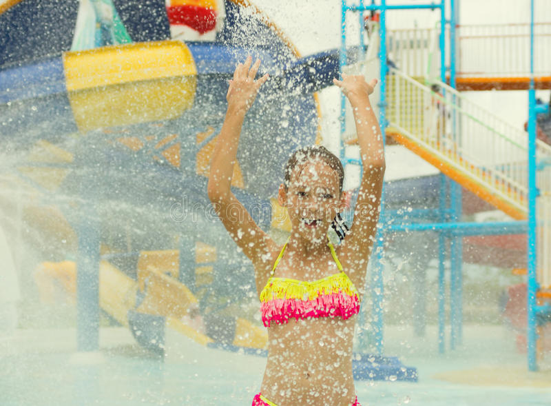 Cheerful preteen girl splashing water towards the camera. Blurred waterpark in background royalty free stock photos