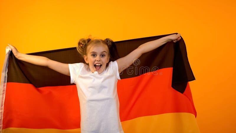 Cheerful preteen girl waving german flag, national sport team winning match stock image