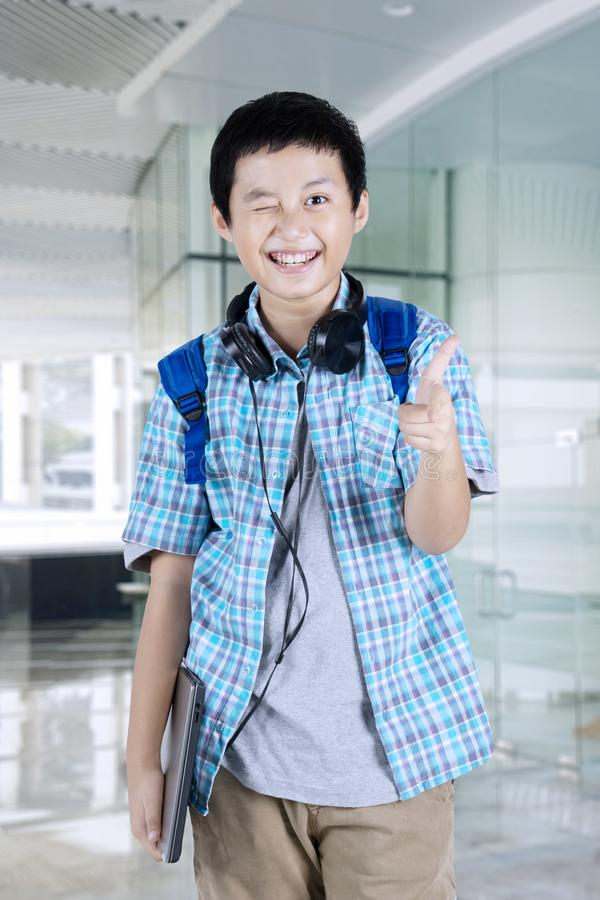 Cheerful preteen student winks at the camera royalty free stock image