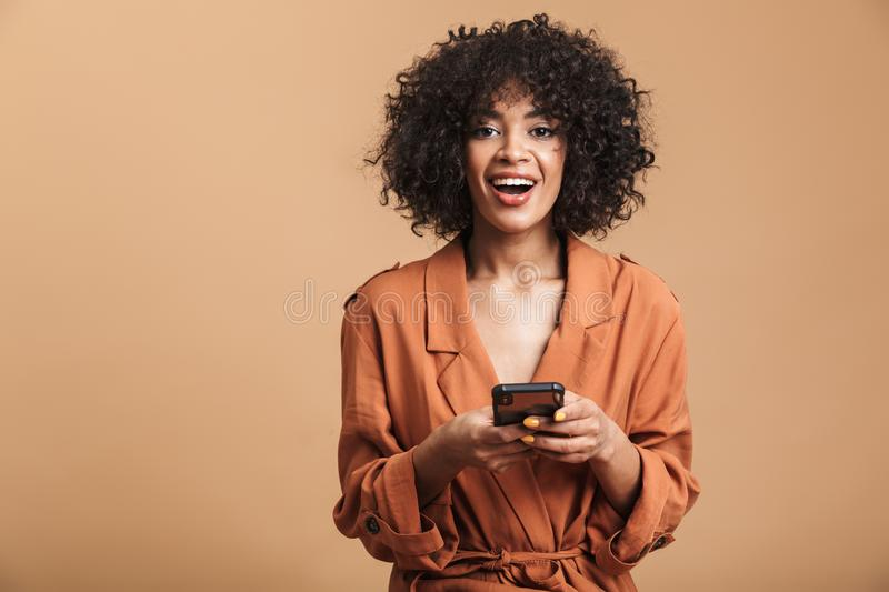 Cheerful pretty african woman holding smartphone and looking at camera. Cheerful pretty african woman holding smartphone and looking at the camera over brown royalty free stock photography