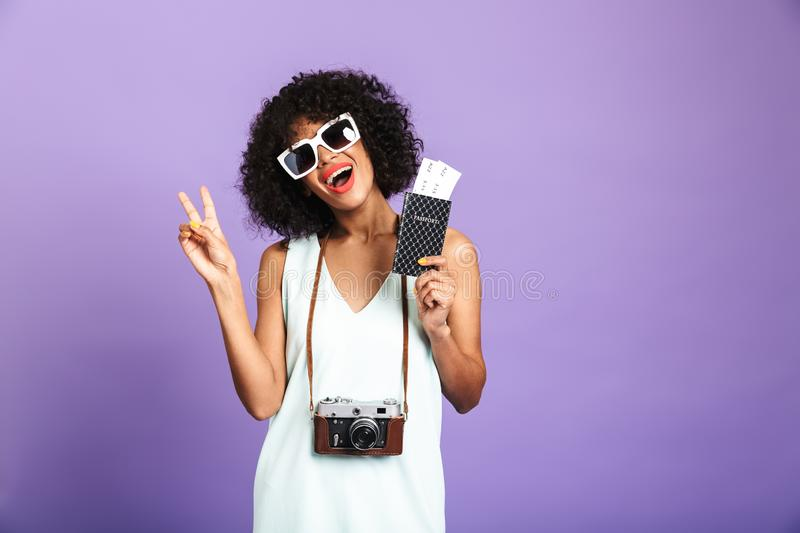 Cheerful pretty african woman in sunglasses preparing to trip. And showing peace gesture while looking at the camera over violet background stock images