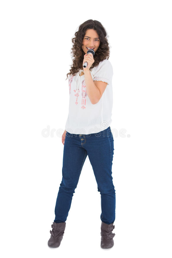 Download Cheerful Pretty Brunette With Microphone Singing Stock Photo - Image of boots, holding: 33107802
