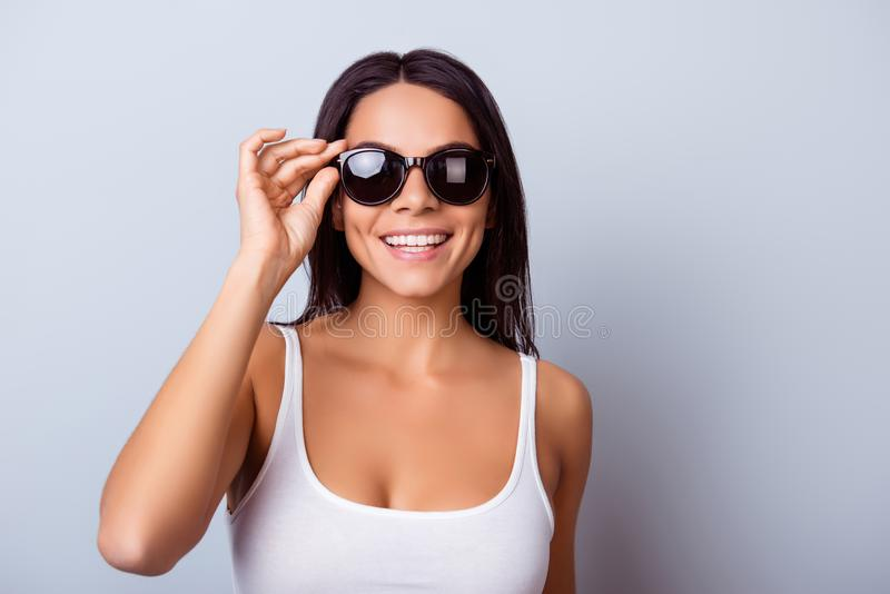 Cheerful pretty latin american lady with beaming smile in stylish spectacles is standing on the light blue background stock images