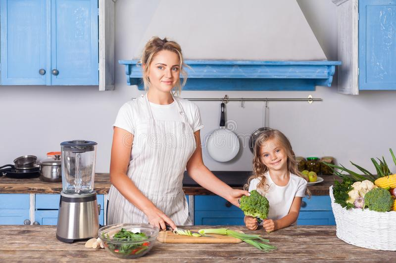 Cheerful pretty mother in apron and little daughter holding broccoli and smiling at camera, cooking salad in modern kitchen. Together, preparing vegetarian food royalty free stock photography