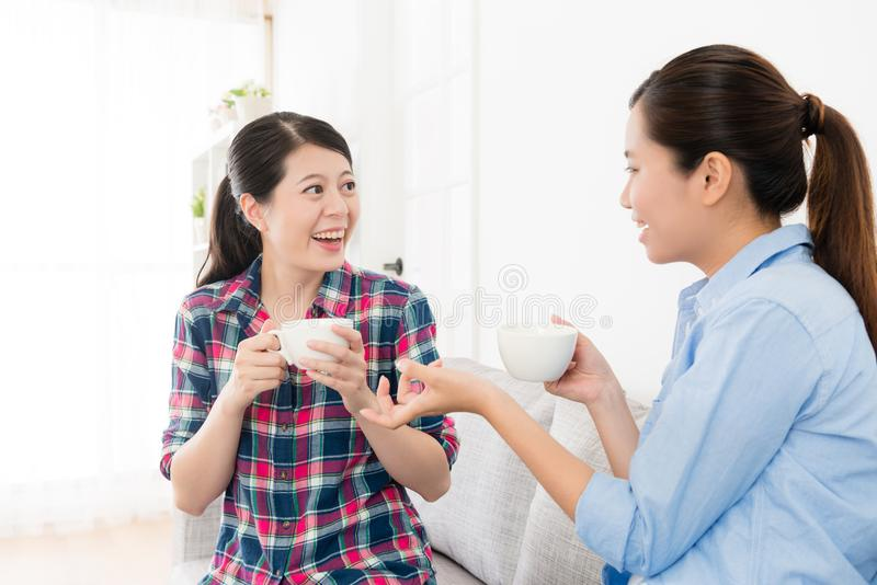 Cheerful pretty sisters sitting on sofa couch. Chatting and drinking hot coffee relaxing during holiday at home in living room stock photo