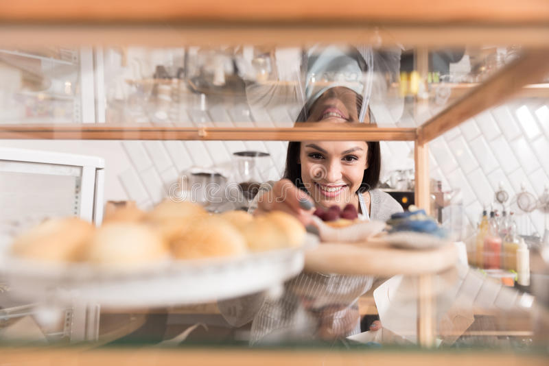 Cheerful pretty smiling woman getting cake from display stand. stock images
