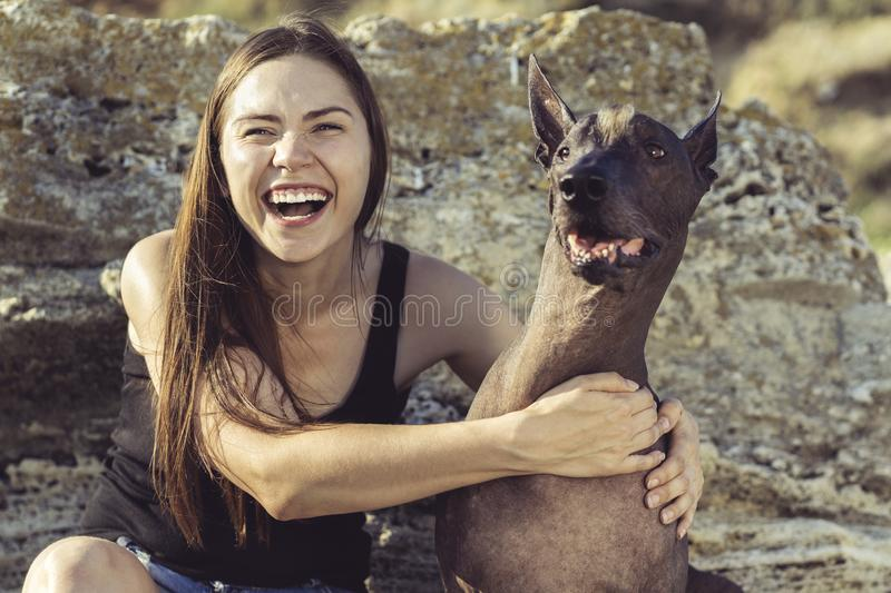 Cheerful pretty young girl sitting and hugging her dog xoloitzcuintli on the stoun beach at sunset stock image
