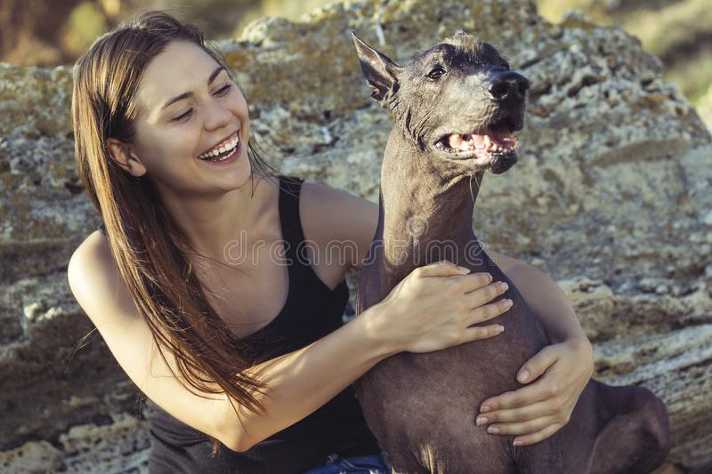 Cheerful pretty young girl sitting and hugging her dog xoloitzcuintli on the stoun beach at sunset royalty free stock images