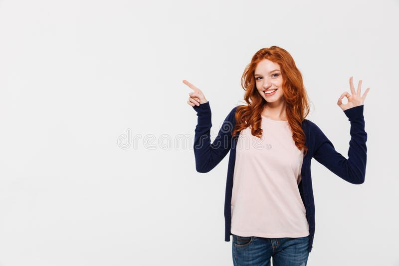 Cheerful pretty young redhead lady showing okay gesture while pointing. stock images