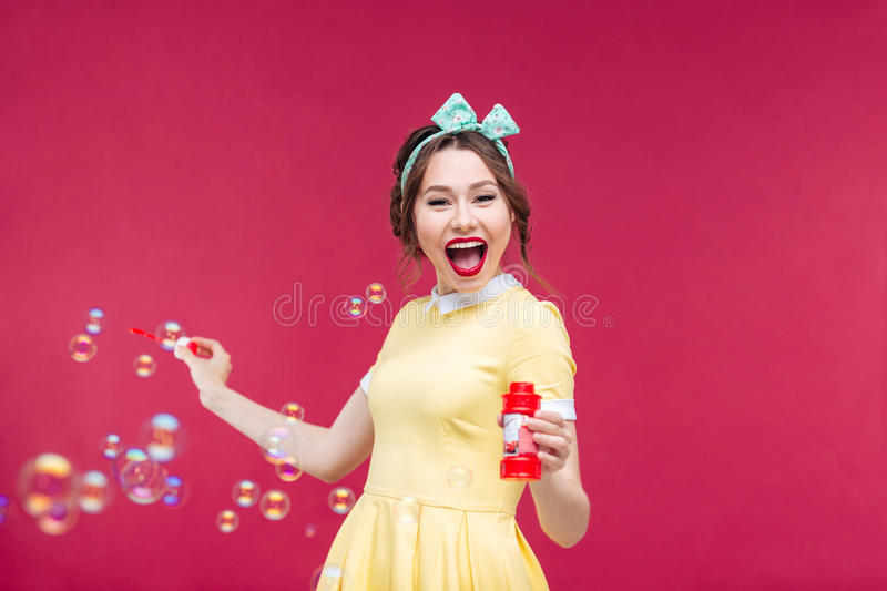 Cheerful pretty young woman having fun with soap bubbles stock photography