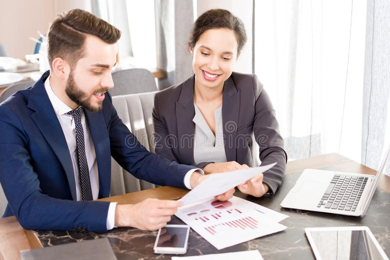 Optimistic forecasting managers discussing papers. Cheerful professional multiethnic analysts in formalwear discussing statistics while viewing report with royalty free stock images