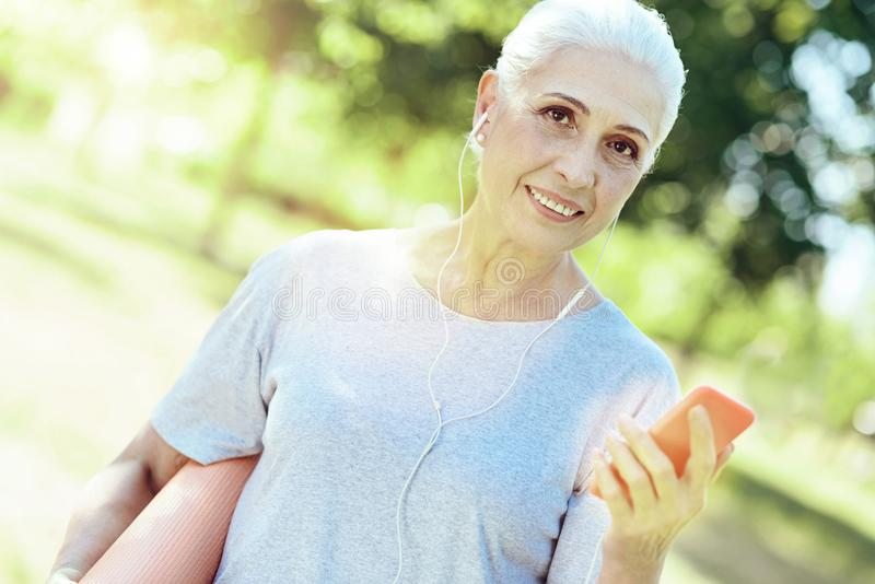 Cheerful progressive pensioner wearing earphones while walking. Wonderful music. Smiling kind progressive pensioner listening to musing while walking in a park royalty free stock photography