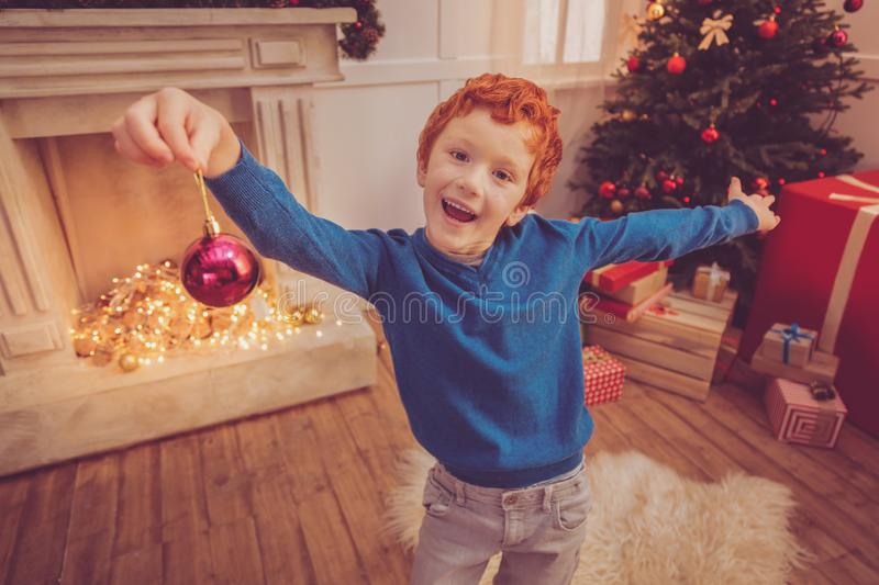 Cheerful red-haired boy posing with a Christmas ball royalty free stock image