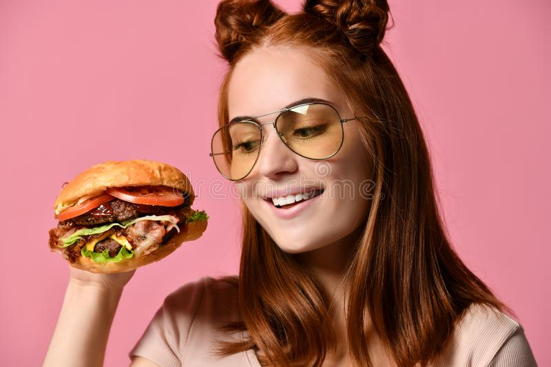 Woman eat burger sandwich with hungry mouth on pink background. Cheerful red-haired girl hungrily looks at her fast food hamburger, closeup portrait, bright royalty free stock images