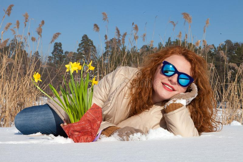 Adorable red haired woman with blue sunglasses expressing calmness while resting in snowdrift stock photo