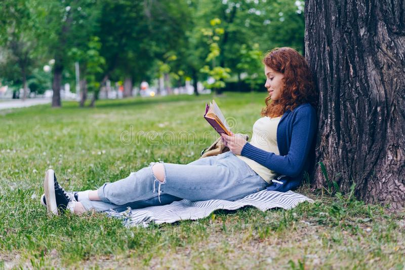 Cheerful redhead girl reading book outdoors in park smiling relaxing on grass stock photos