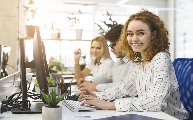 Cheerful redhead office manager smiling to camera stock photos