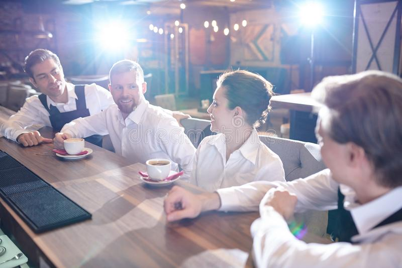 Cheerful restaurant staff chatting and drinking coffee after wor stock images