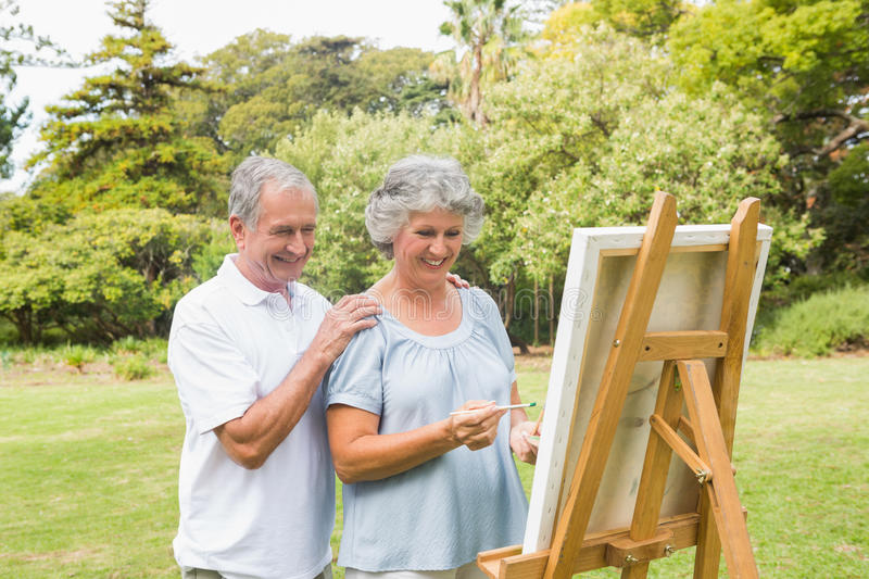 Cheerful Retired Woman Painting On Canvas With Husband Stock Images