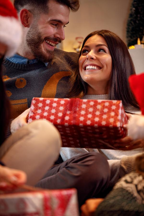 Romantic couple exchanging gift boxes at Christmas eve royalty free stock image