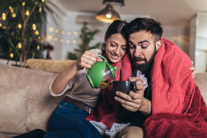 Romantic couple is sitting on sofa under cozy plaid and smiling. They are drinking tea. Cheerful romantic couple is sitting on sofa under cozy plaid and smiling stock photography