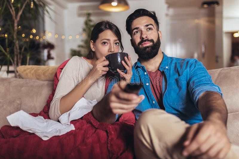 Romantic couple is sitting on sofa under cozy plaid and smiling. They are drinking tea and watching tv. Cheerful romantic couple is sitting on sofa under cozy stock photos