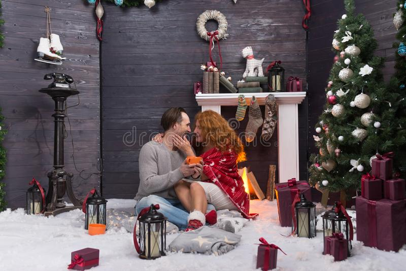 Happy woman in warm blanket sitting near fireplace and hugging her husband. Cheerful romantic women hugging her husband on the carpet near the fireplace while stock images