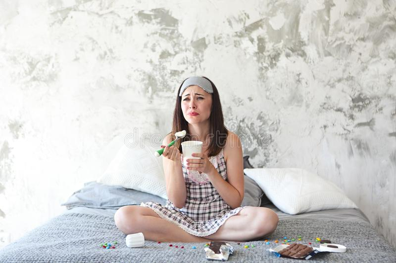 Cheerful sad young craing woman eating sweets in her bedroom. Chocoholic. Cheerful sad young craing woman eating sweets in her bedroom. Emotional woman with stock photo