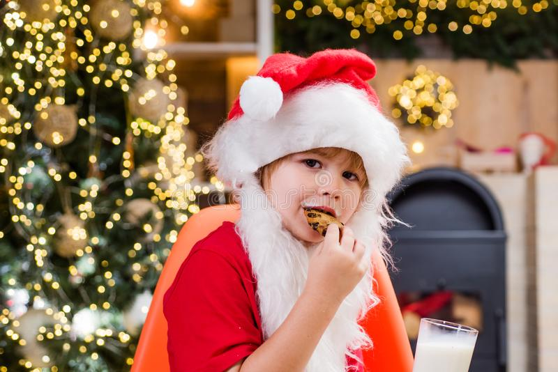 Cheerful Santa Claus holding glass with milk and cookie with fireplace and Christmas Tree in the background. Cookies for. Kids Santa Claus royalty free stock images